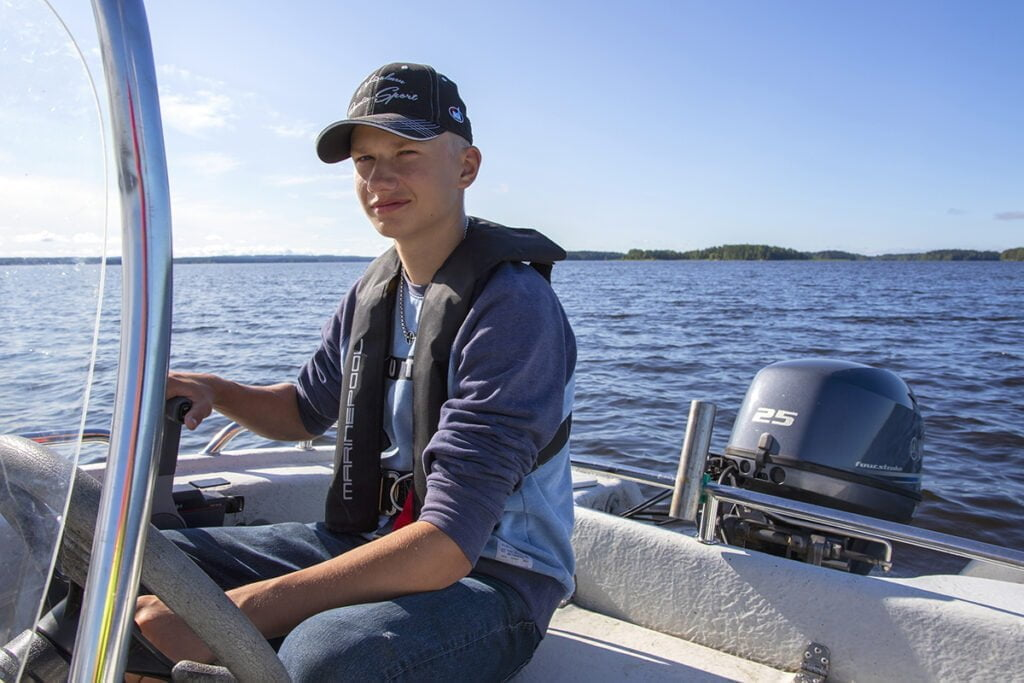 Nuori mies istuu järvellä moottoriveneessä.