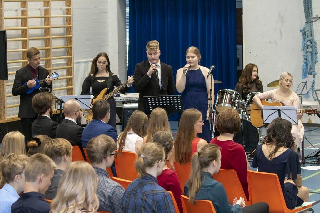 Harrasteakatemian bändi esitti lakkiaisjuhlassa musiikkia opettaja Arto Riihijärven (vas.) johdolla.