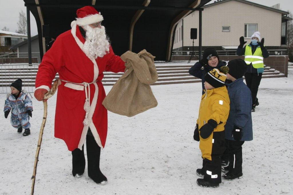 Joulupukki säkkeineen ja lapset.