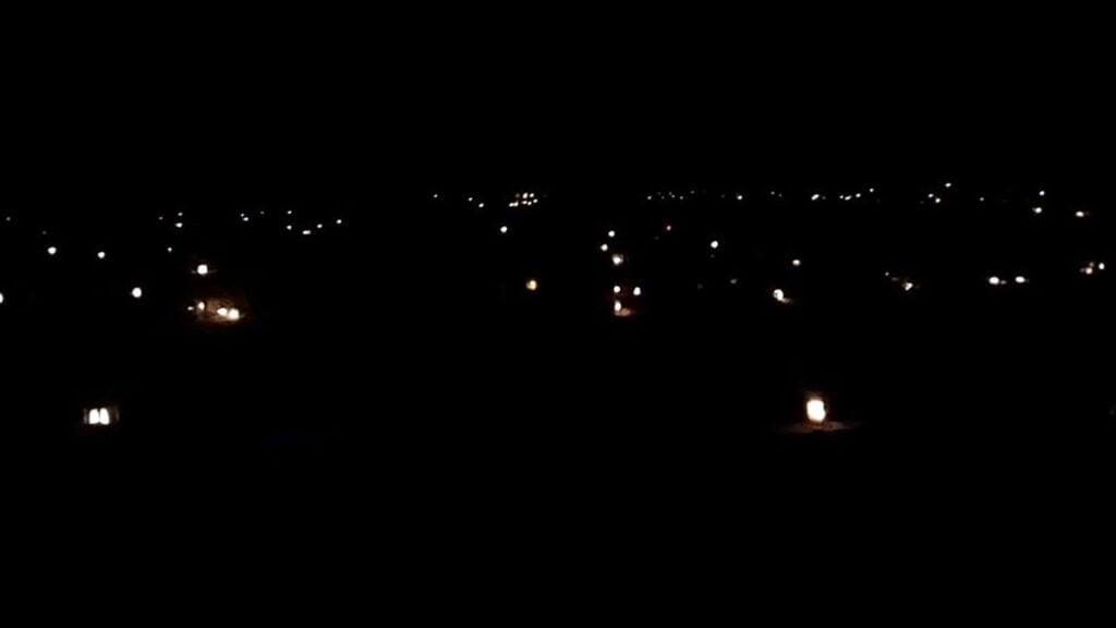 Hautakynttilöiden valopilkkuja pimeässä.