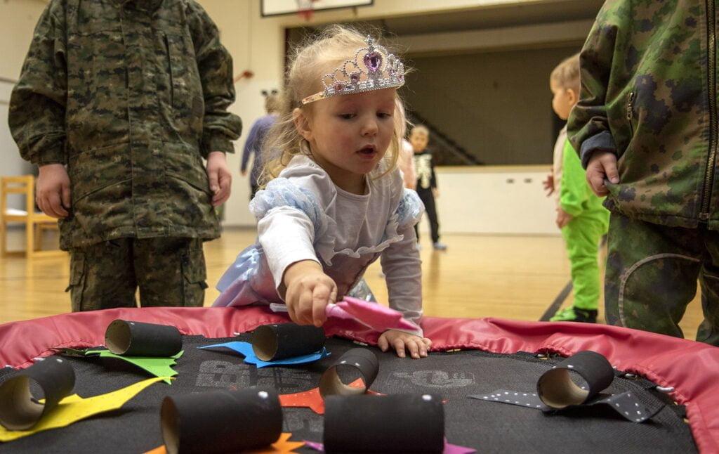 """Lapset leikkivät, prinsessavaatteisiin pukeutunut pikkutyttö osoittaa taikasauvalla vessapaperista askarreltuja """"lepakoita"""""""