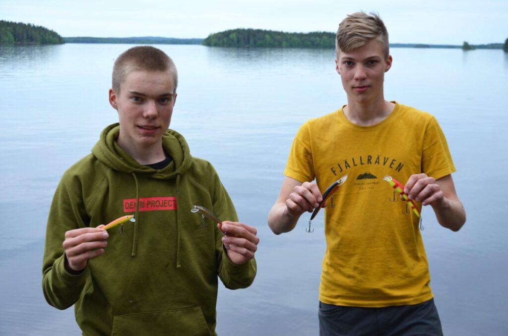 Nuoret miehet seisovat järven rannalla, molemmilla vaaput käsissään.